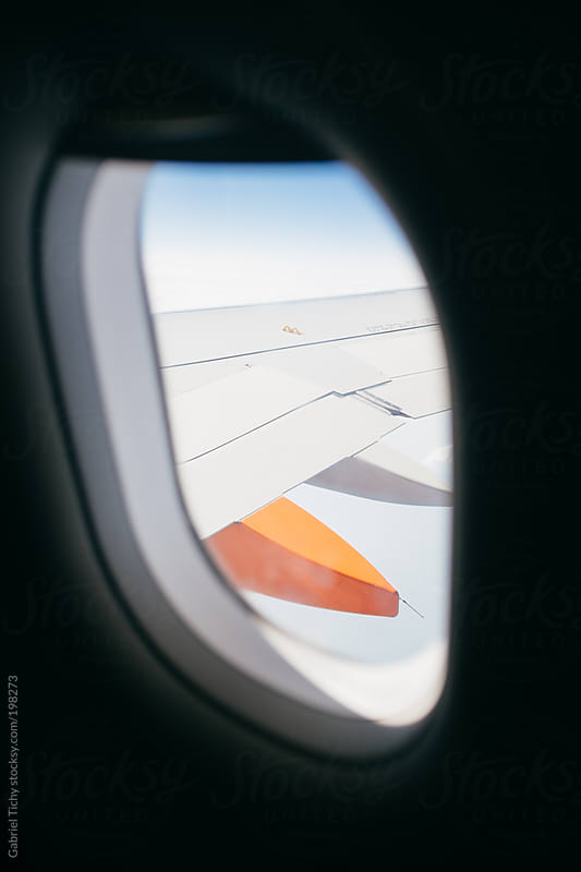 Wing through an airplane window by Gabriel Tichy for Stocksy United