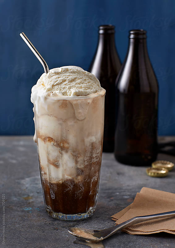 Vanilla ice cream float with drip with brown bottles, metal surface and blue background by Sherry Heck for Stocksy United