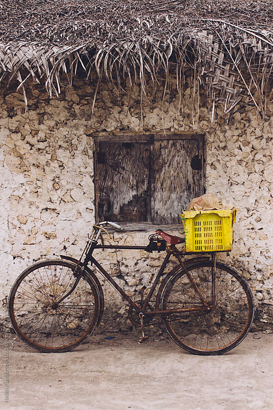 Bicycle leaning against the wall of a traditional African mud house. by Helen Rushbrook for Stocksy United