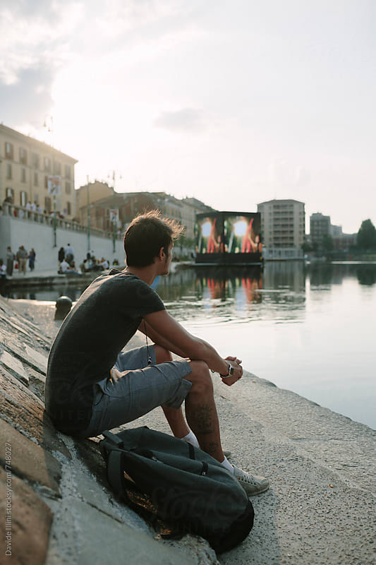 Young man sitting on the bank of a canal in the city at sunset by Davide Illini for Stocksy United