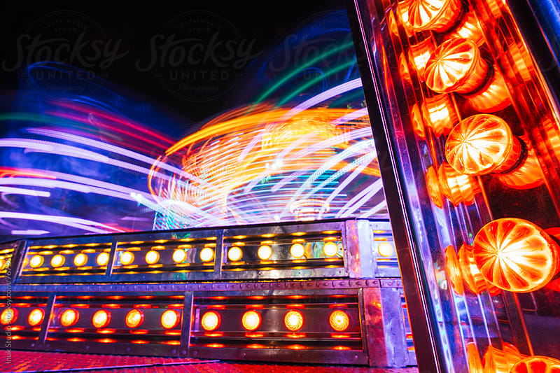 Carousel in an amusement park at night with colourful lights in motion by Inuk Studio for Stocksy United