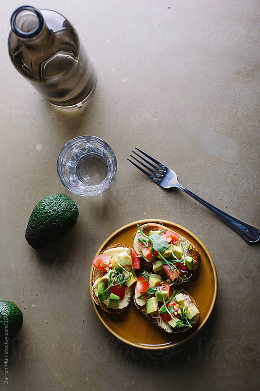 Avocado,tomato and samphire toasts on a plate.Avocado toast brunch. by Darren Muir for Stocksy United
