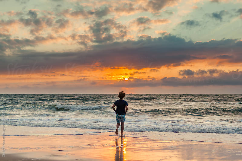 Silhouette of a boy from the back walking on the beach during sunset by Cindy Prins for Stocksy United