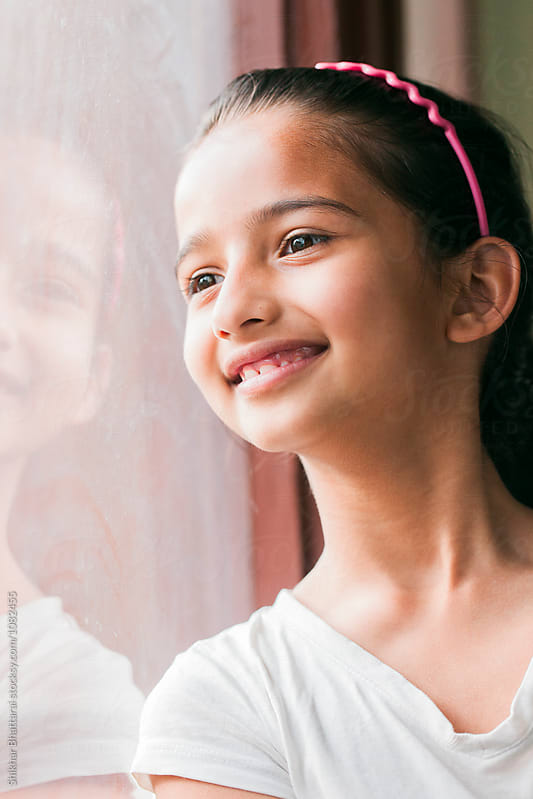 Portrait of a young girl looking outside the window. by Shikhar Bhattarai for Stocksy United
