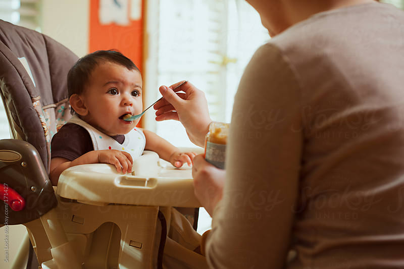 Baby: Mother Feeds Infant In High Chair by Sean Locke for Stocksy United