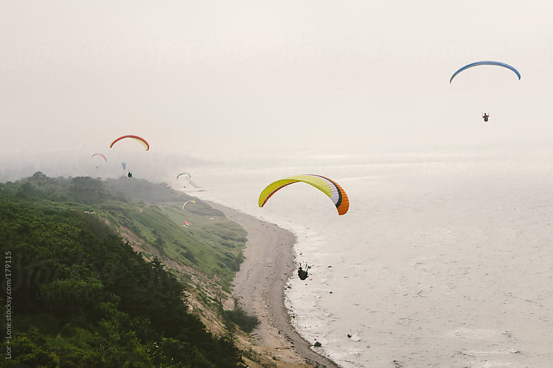 Paragliders flying over the coast by Lior + Lone for Stocksy United