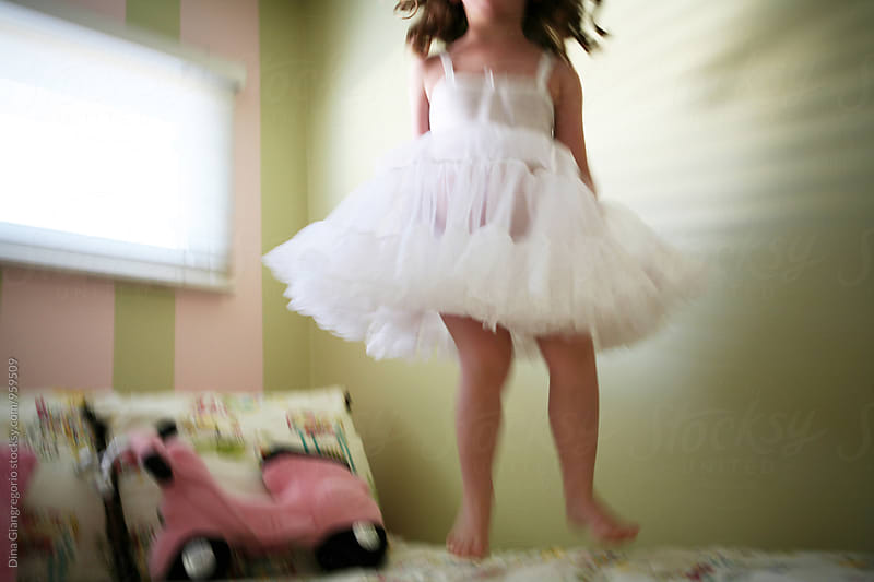 Girl In White Slip Dress Jumping On Bed by Dina Giangregorio for Stocksy United