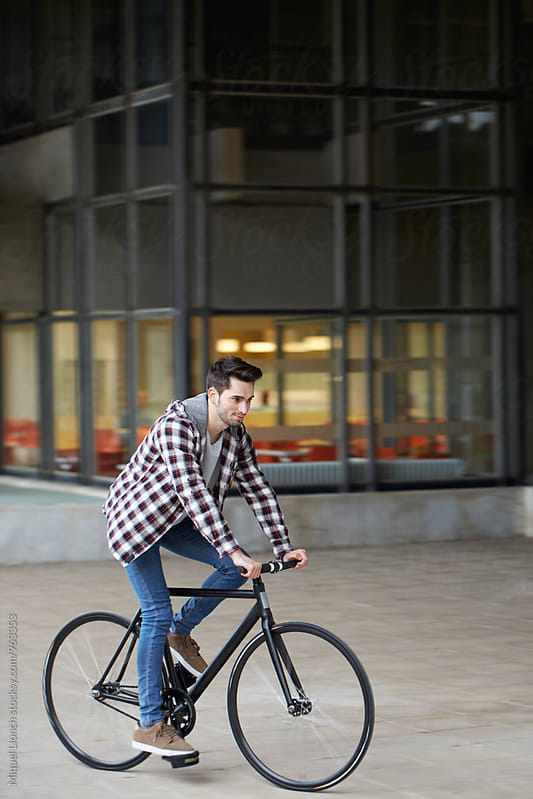 Young man riding a bike nearby a building in the campus by Miquel Llonch for Stocksy United