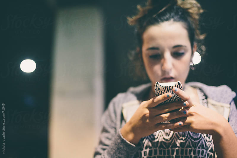 Teenage girl text messaging on her phone. by michela ravasio for Stocksy United