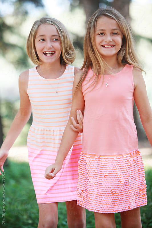 Happy fraternal twin sisters wearing dresses laughing by Dina Giangregorio for Stocksy United