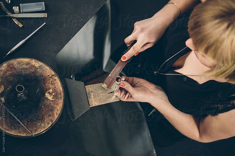 Jewelry designer working on a new piece in her workshop shot from above by Lior + Lone for Stocksy United