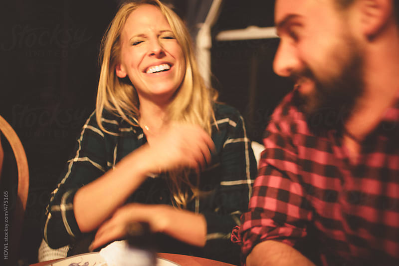 Friends laughing at dinner party by HOWL for Stocksy United