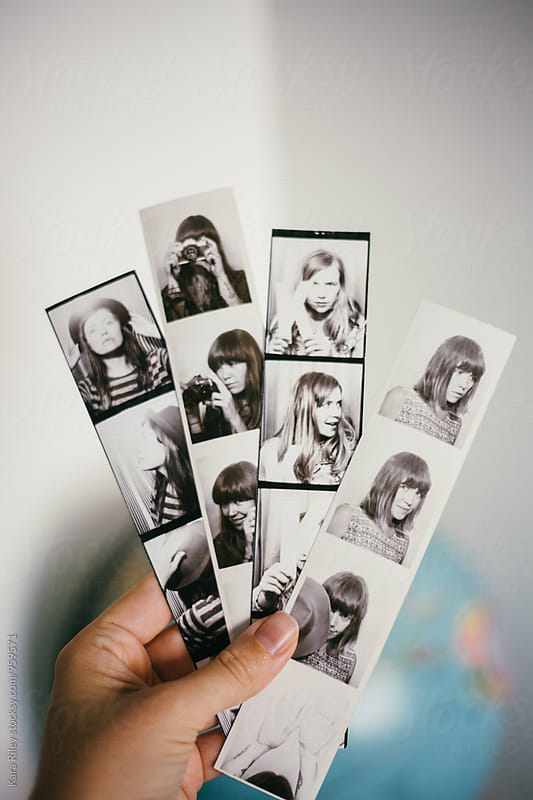 Hand holding photobooth strips by Kara Riley for Stocksy United