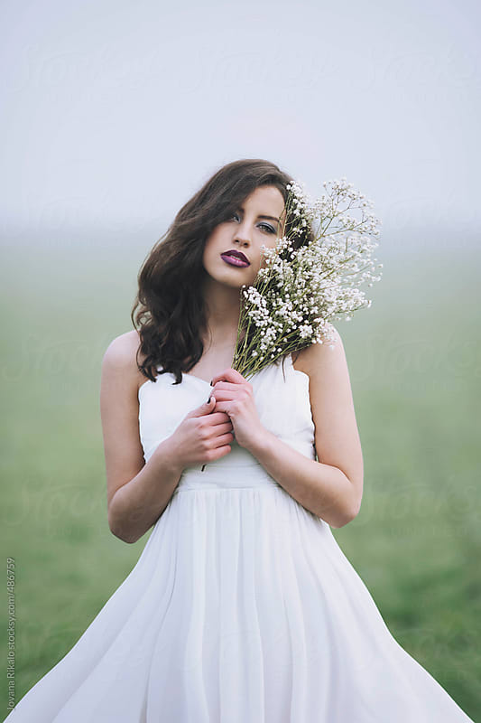 Beautiful young woman holding a flower bouquet by Jovana Rikalo for Stocksy United