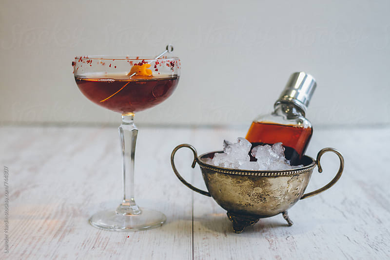 classic manhattan cocktail in a coupette and in a flask on the rocks by Leander Nardin for Stocksy United