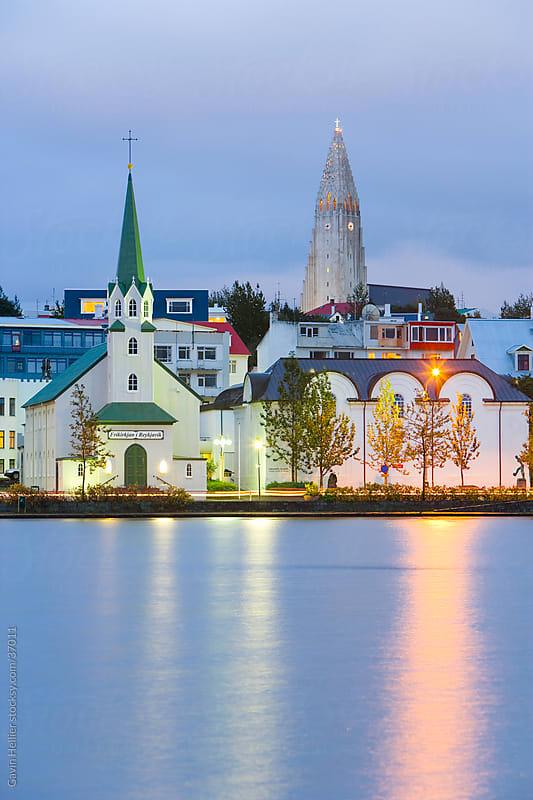 Iceland, Reykjavik, The tin-clad Frikirkjan i Reykjavik church and Hallgrimskirkja looming above the city viewed across lake Tjorn illuminated at dusk by Gavin Hellier for Stocksy United