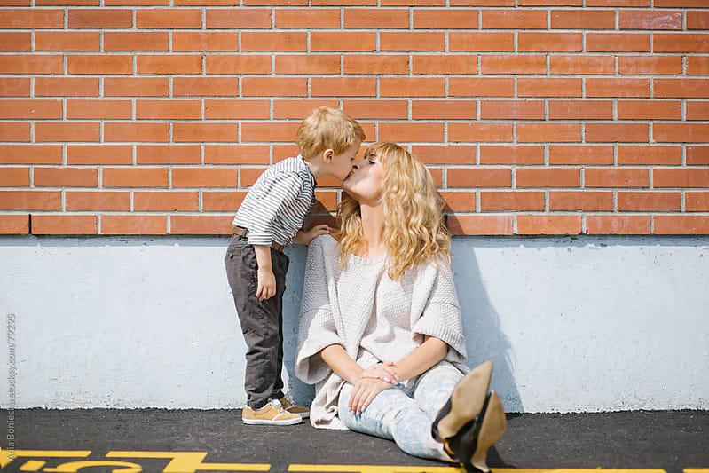Son kissing his mum at a school playground by Ania Boniecka for Stocksy United
