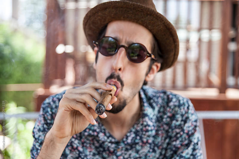 Young man wearing fedora smoking cigar by Lisa MacIntosh for Stocksy United