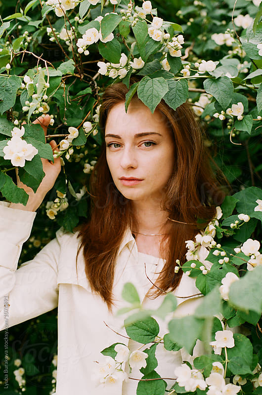 Portrait of young woman among jasmine by Lyuba Burakova for Stocksy United