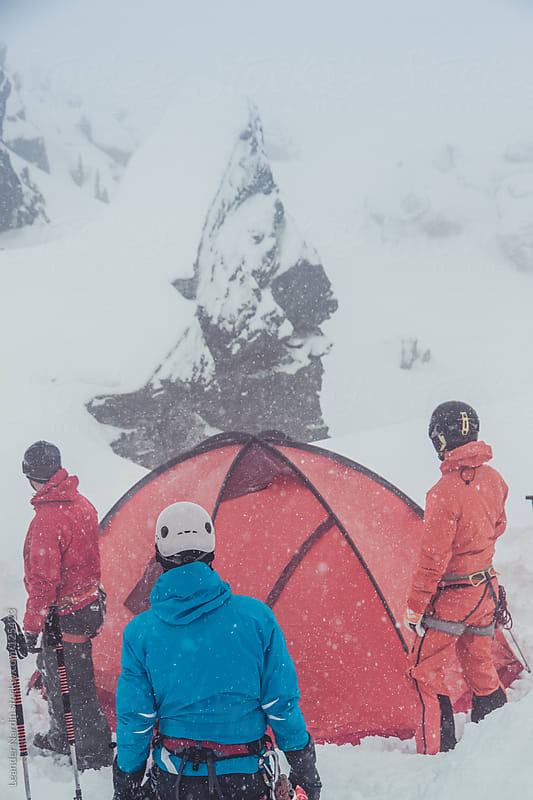 group of freeskier set up a tent during a snowstorm by Leander Nardin for Stocksy United