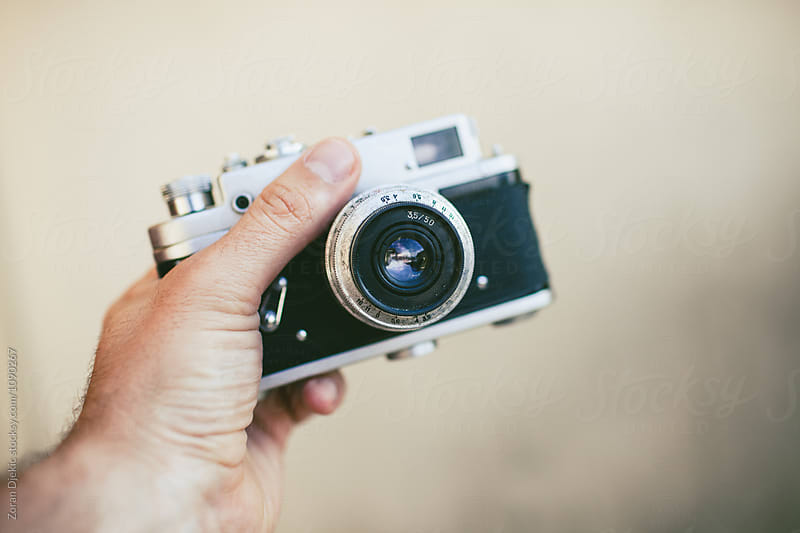 Hand holding an old vintage film camera  by Zocky for Stocksy United
