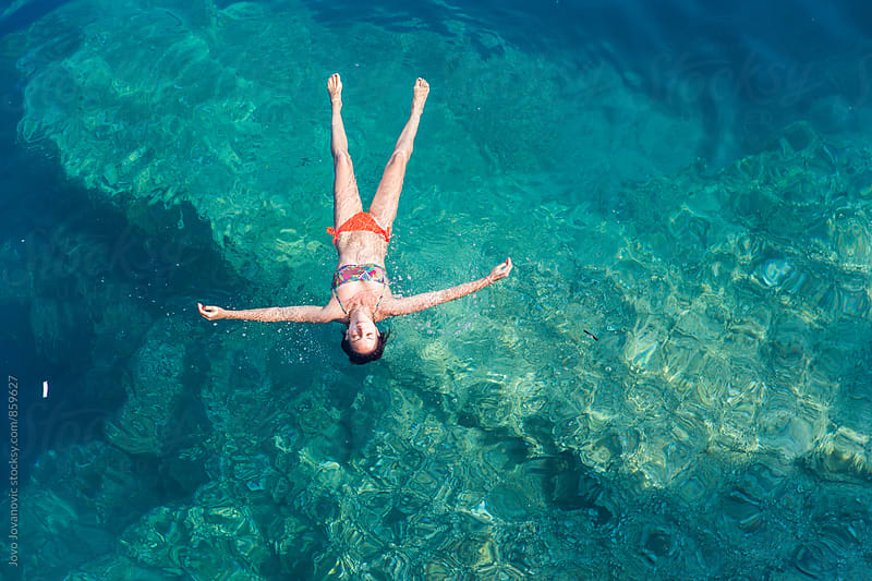 Beautiful young woman in a bikini floating in the ocean water and relaxing  by Jovo Jovanovic for Stocksy United