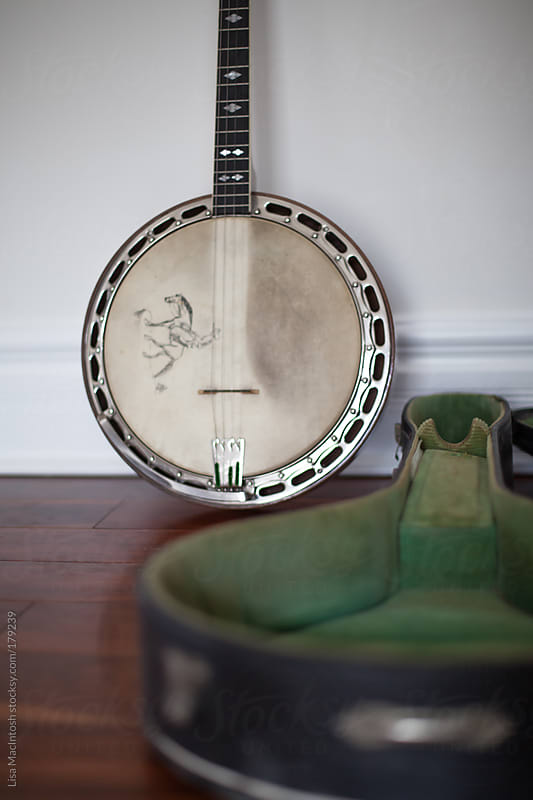 vintage banjo leaning against wall with case by Lisa MacIntosh for Stocksy United