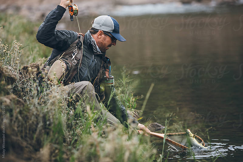 fly fisherman netting a caught fish by the river by Micky Wiswedel for Stocksy United