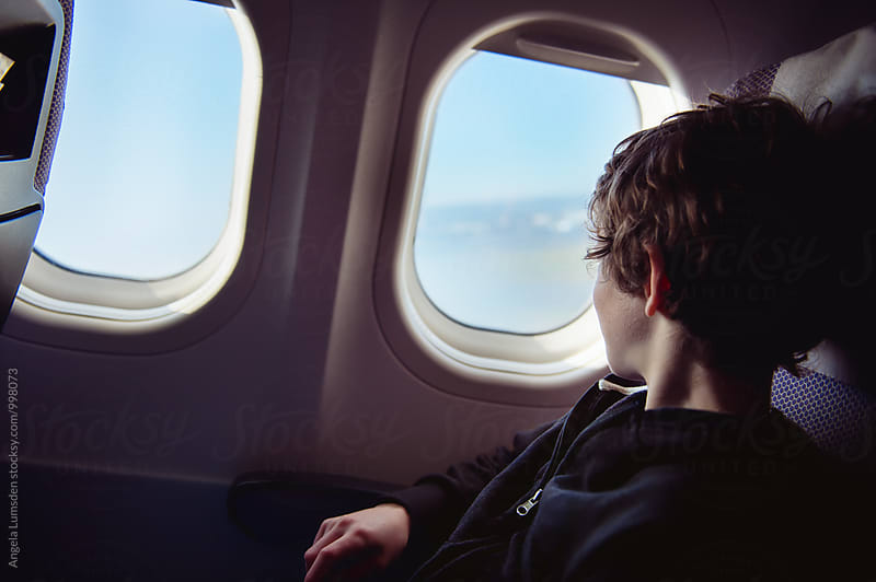 Boy in a window seat looking out the  window as a plane takes off by Angela Lumsden for Stocksy United