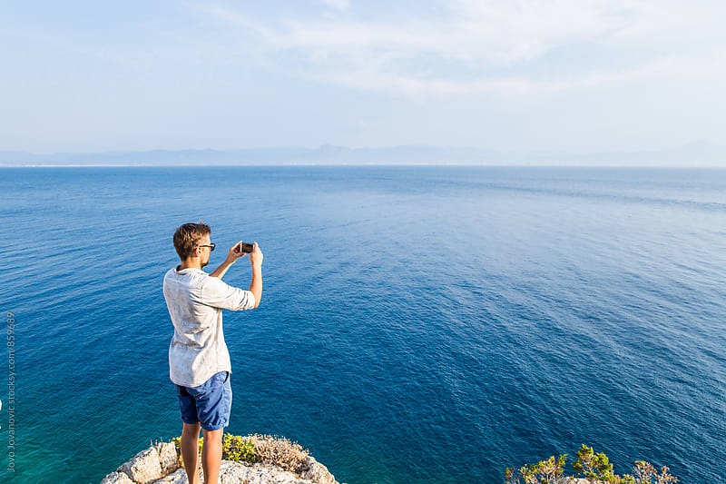 Handsome young man in a white shirt and blue shorts taking a photo of the ocean horizon  by Jovo Jovanovic for Stocksy United