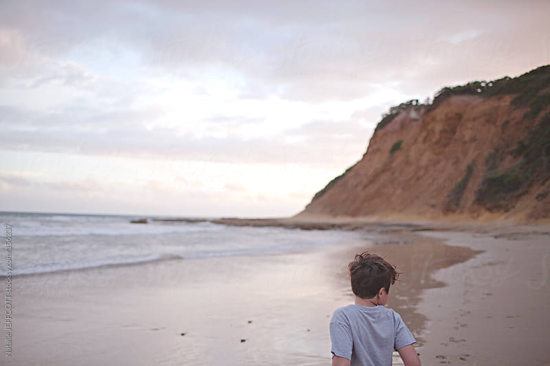 young boy looking out to sea during sunset on a beach in Australia by Natalie JEFFCOTT for Stocksy United