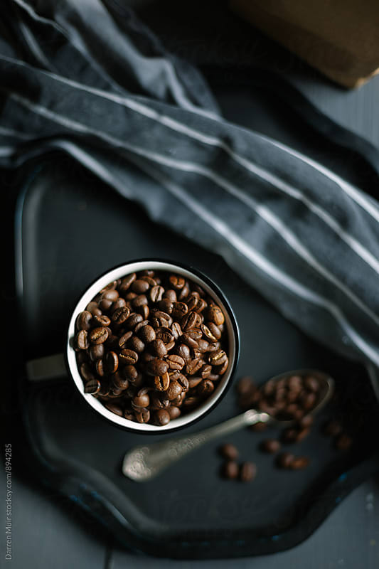 Coffee beans in a mug. Seen from overhead. by Darren Muir for Stocksy United