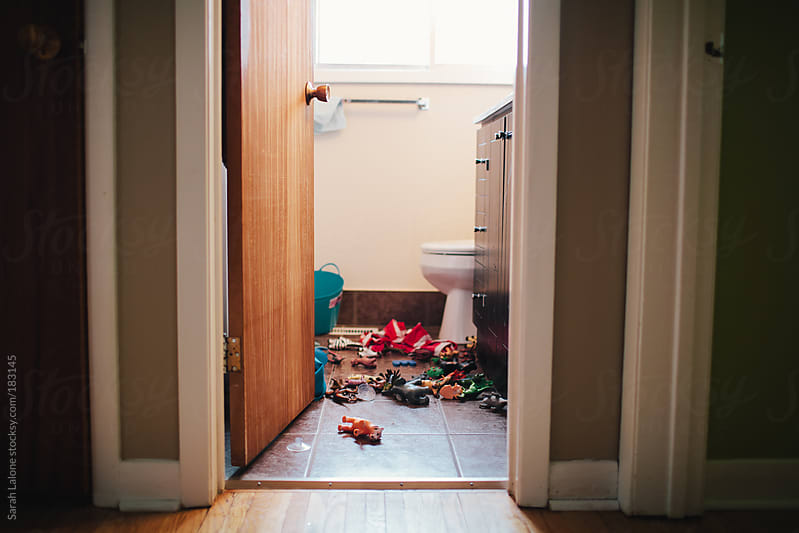 bath toys on the floor in a bathroom by Sarah Lalone for Stocksy United