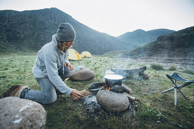 outdoorsman stoking a cooking fire whilst camping in the mountains by Micky Wiswedel for Stocksy United
