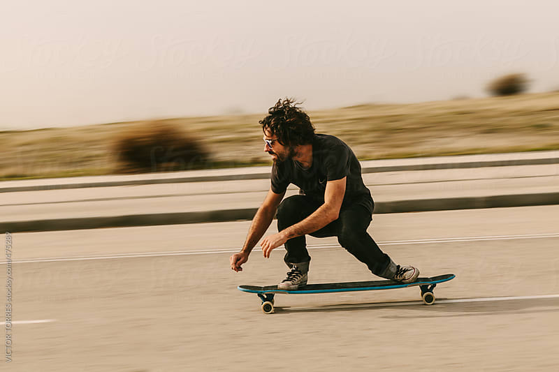 Young Man Longboarding in the Streets by VICTOR TORRES for Stocksy United