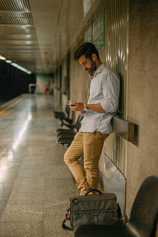 Man waiting for a train and using phone. by Studio Firma for Stocksy United