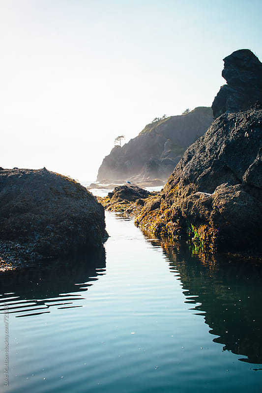 A Calm Blue Tidal Pool Rests Under The Shadows Of Rock Formations by Luke Mattson for Stocksy United