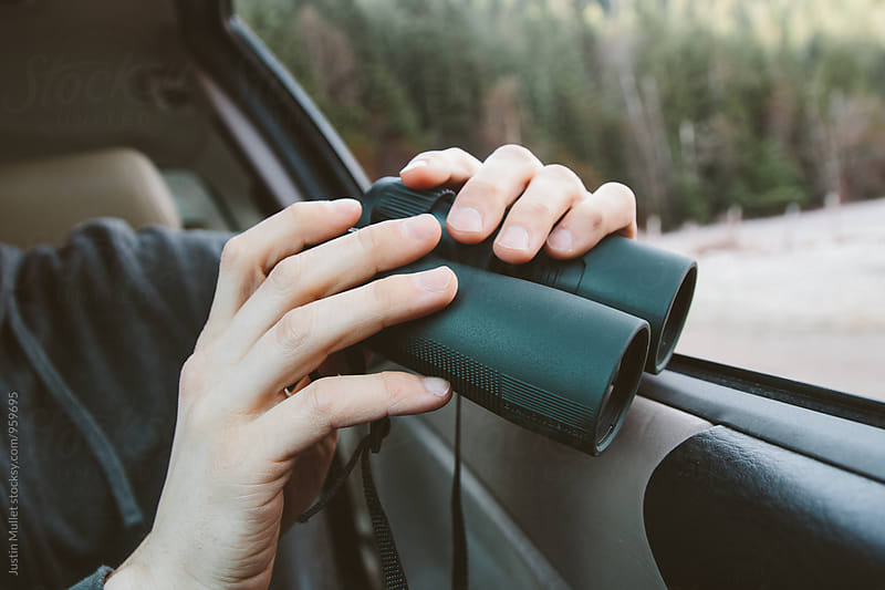 Close up of young man holding binoculars in car by Justin Mullet for Stocksy United