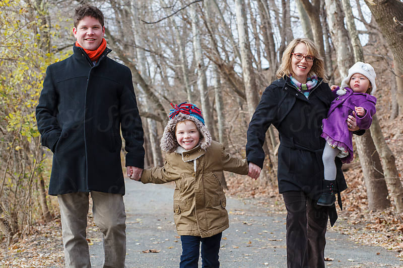 Young Family Holding Hands Walks Down Path by Holly Clark for Stocksy United