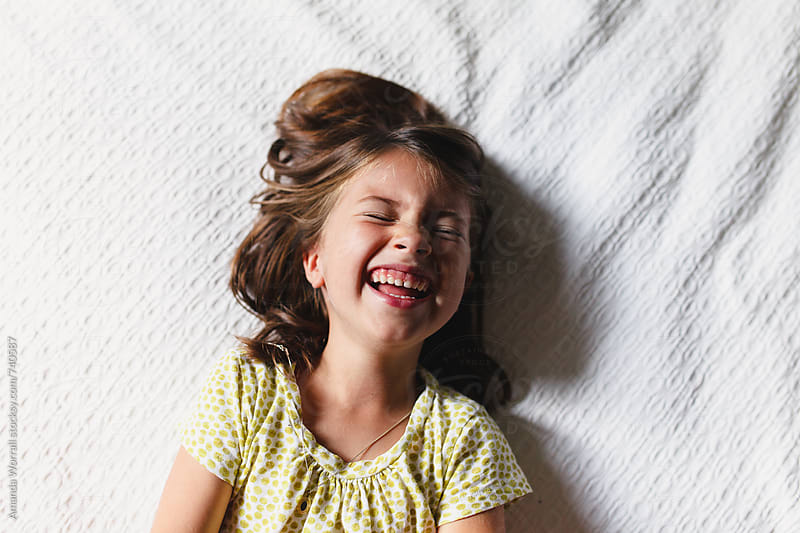 5 year old giggling indoors by Amanda Worrall for Stocksy United