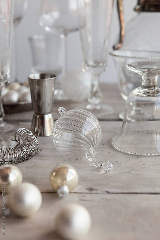 Silver and white christmas holiday drinks table with select focus on Christmas bauble decoration by Nadine Greeff for Stocksy United