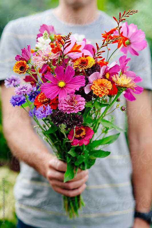 Man holding a bunch of flowers by Suzi Marshall for Stocksy United