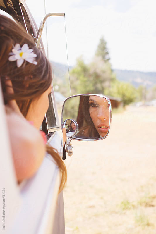 A woman leans out the window to look at herself in the car's mirror by Tana Teel for Stocksy United