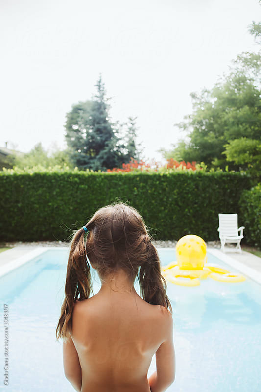 Girl playing in a swimming pool by Giada Canu for Stocksy United
