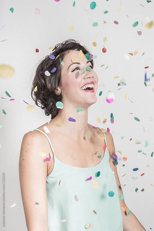 Woman Laughing as Confetti Falls from Above by suzanne clements for Stocksy United