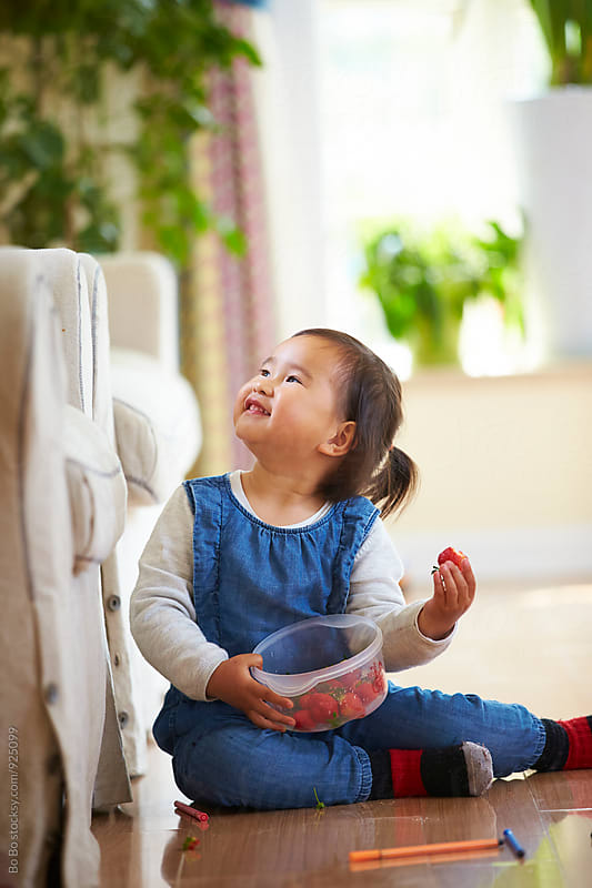 happy little girl eating strawberry indoor by cuiyan Liu for Stocksy United