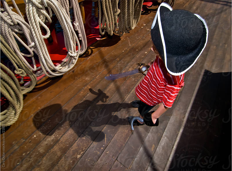 Young boy dressed up as pirate watches his shadow by Cara Slifka for Stocksy United
