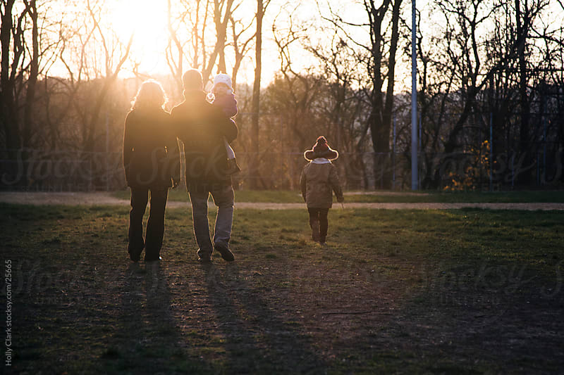 Family stands in field while watching sunset by Holly Clark for Stocksy United