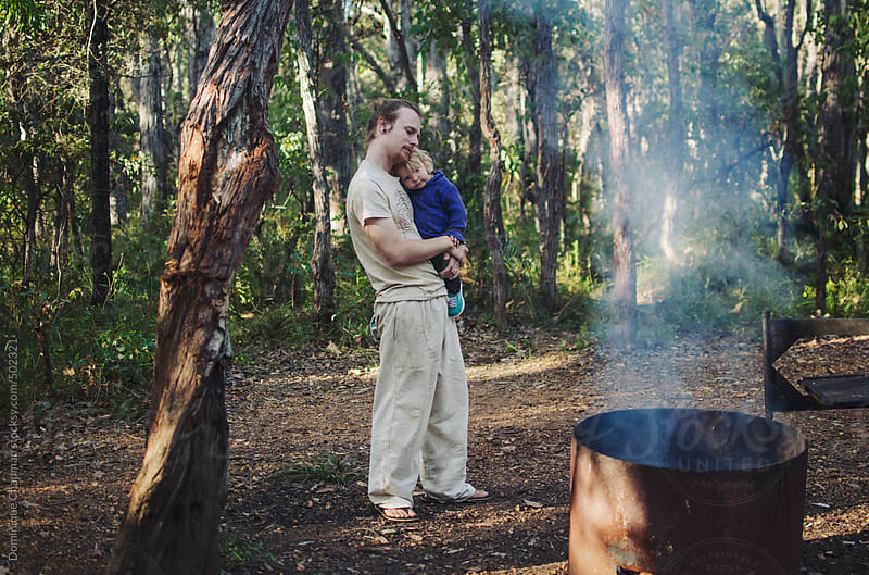 Father and child cuddling by campfire by Dominique Chapman for Stocksy United