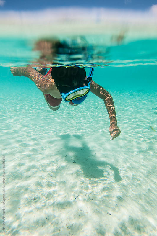 Boy snorkelling in a tropical lagoon, Rarotonga Island, Cook Islands. by Thomas Pickard for Stocksy United